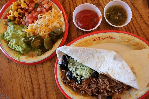 a beef burrito with various toppings on a side plate