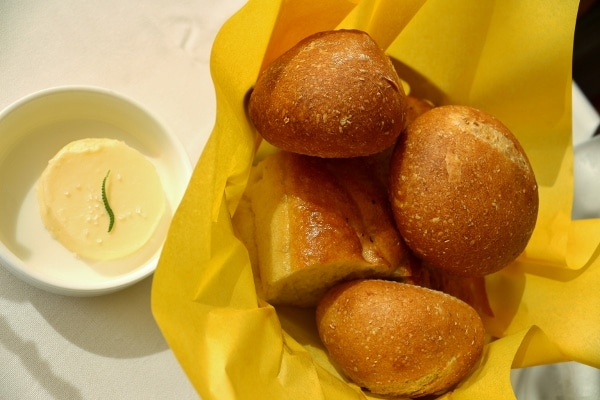 a bread basket, and a pat of butter in a small dish