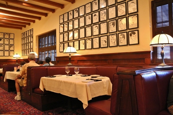 a table in a restaurant with lots of framed illustrations on the wall above