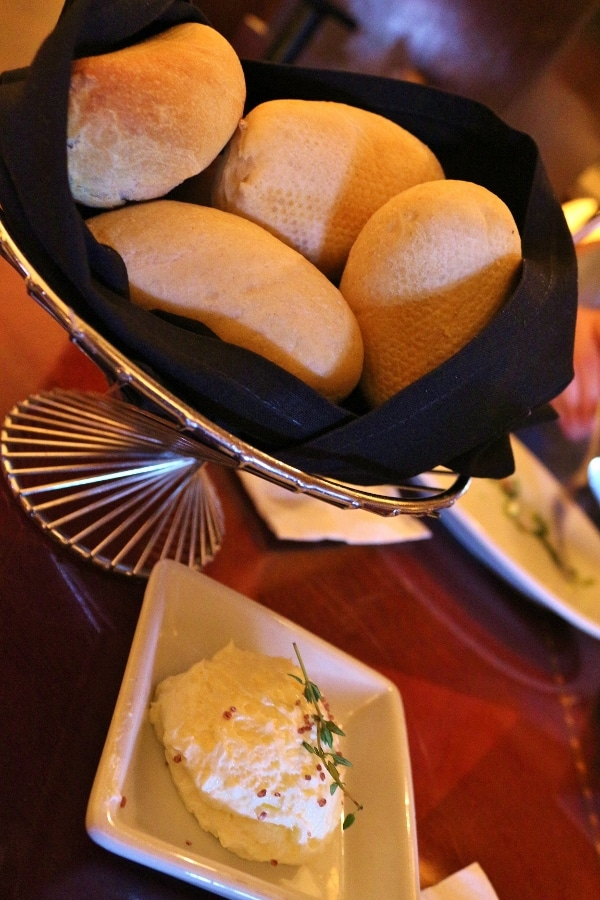 a bread basket and a dish of soft butter
