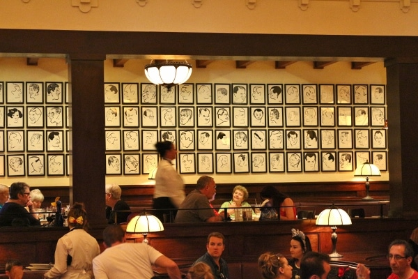 a restaurant dining room filled with people with framed drawings on a distant wall