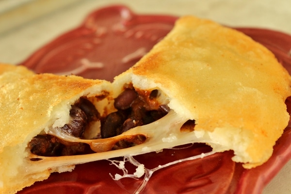 A close up of an empanada broken in half to show the filling