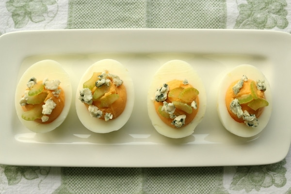 overhead view of a white rectangular plate of deviled eggs with blue cheese and celery