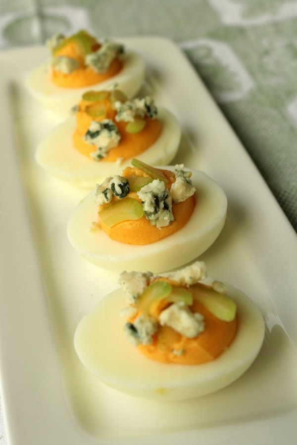 a row of deviled eggs on a white rectangular plate