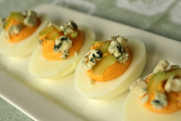a closeup of deviled eggs with blue cheese and celery garnish on a white plate