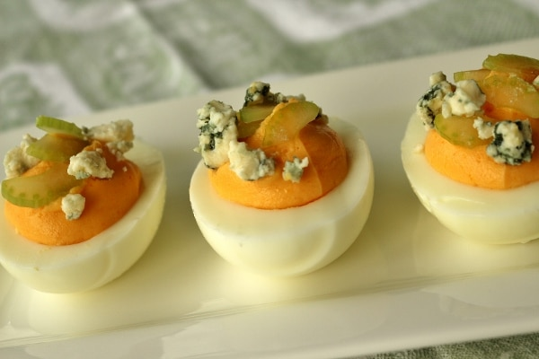 side view of a plate of buffalo deviled eggs with celery and blue cheese on top
