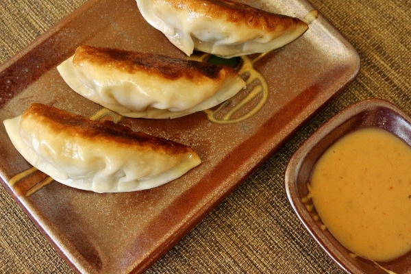 a closeup of fried dumplings on a dark-colored plate with dipping sauce on the side