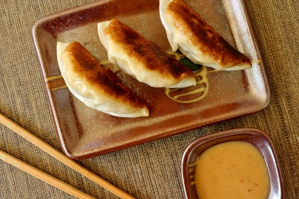 overhead view of pan-fried dumplings on a plate with chopsticks and sauce
