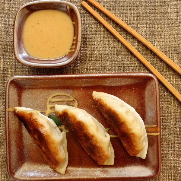 overhead view of three pan-fried dumplings with chopsticks and dipping sauce