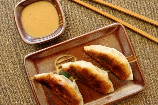 three fried dumplings on a rectangular plate with chopsticks and dipping sauce