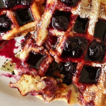 A plate of half-eaten waffles topped with powdered sugar and blueberry syrup.