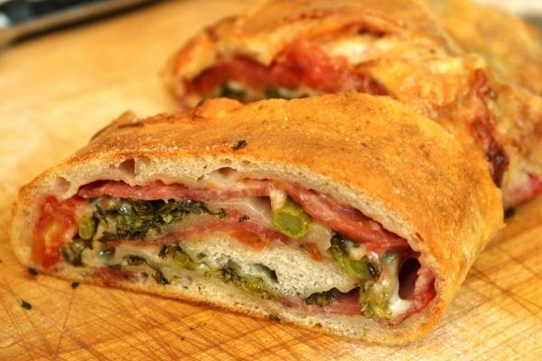 a closeup of slice of stromboli showcasing the filling of soppressata, broccoli rabe, and provolone cheese