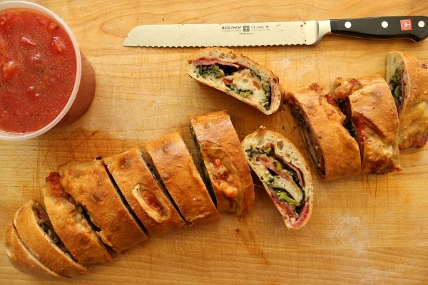 overhead view of a sliced stromboli with a bread knife on a wooden cutting board