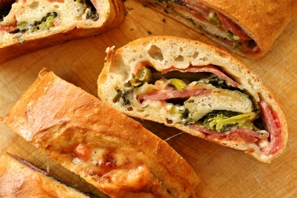 a closeup of a sliced stromboli stuffed with soppressata, rapini, and provolone cheese