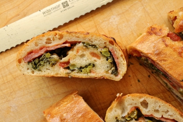 a closeup of a slice of stromboli with broccoli rabe and cheese peeking through