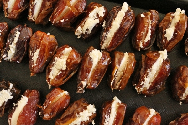 rows of dates stuffed with goat cheese on a black tray