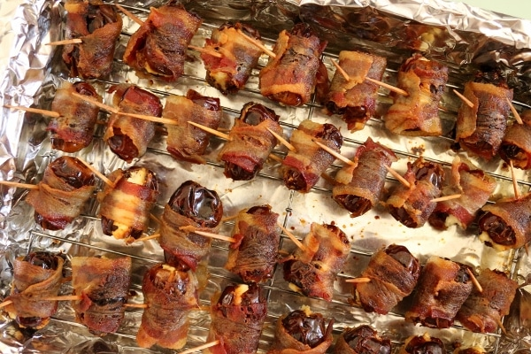 cooked bacon-wrapped dates on a baking sheet