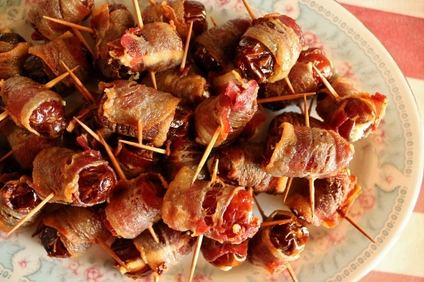 overhead view of a platter of bacon-wrapped dates stuffed with goat cheese