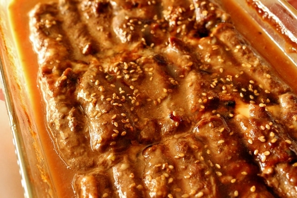 a closeup of a baking dish of beef negimaki with sesame seeds on top