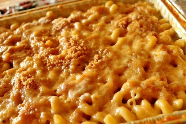 A close up of macaroni and cheese in a foil baking dish