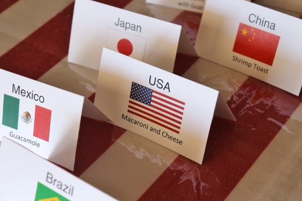 A close up of folded cards with flags, and country and food names printed on them