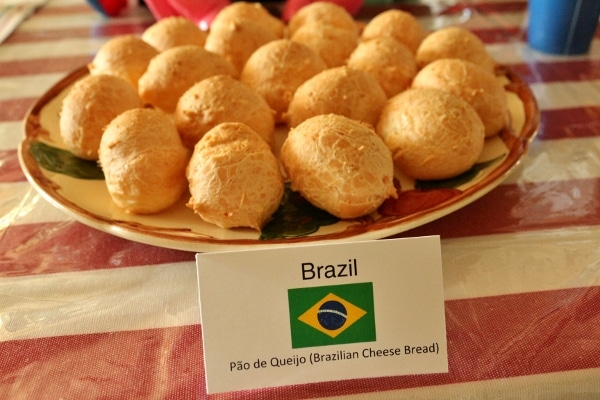 a platter of Brazilian cheese bread with a sign in front saying what it is