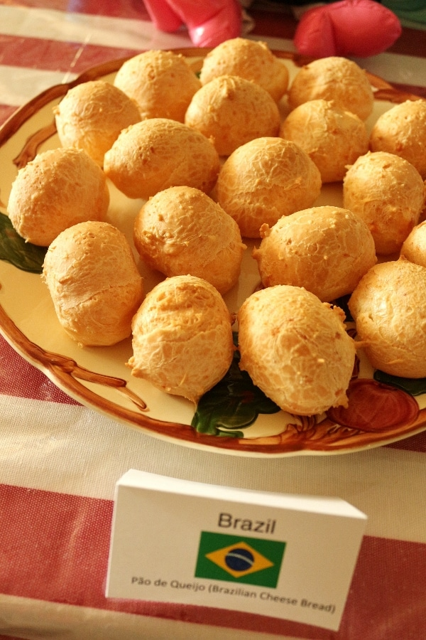 a platter of Pão de queijo (Brazilian cheese bread) with a sign saying what it is