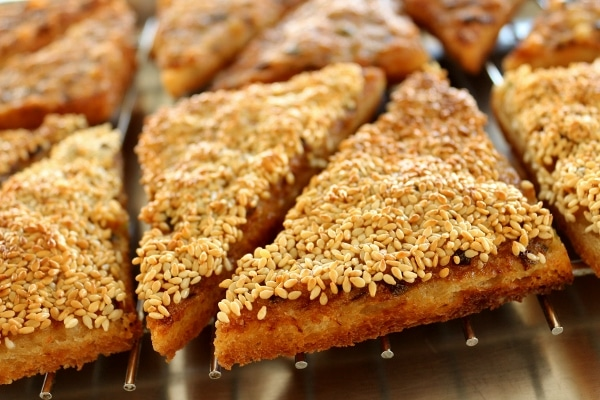 closeup of fried shrimp toasts topped with sesame seeds