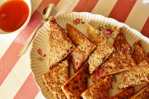 a platter of shrimp toast triangles with sauce in a bowl on the side