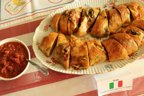 sliced stromboli on a platter with sauce on the side