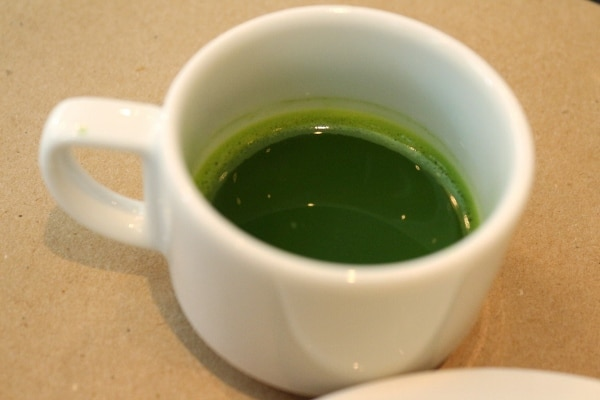 A close up of a small cup of matcha tea
