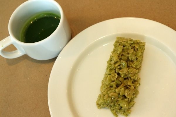 a cup of matcha tea and a matcha rice krispie treat on a plate
