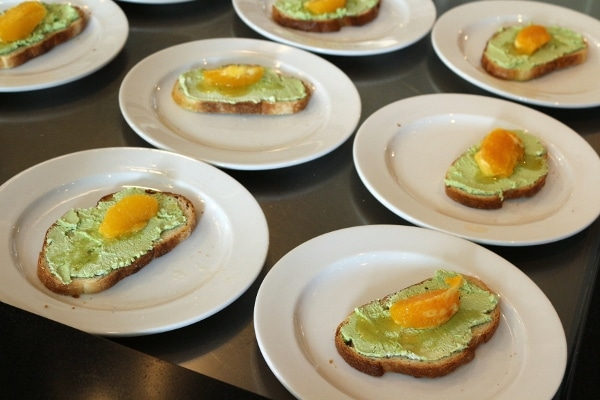 rows of plates topped with toast with green topping and orange segments