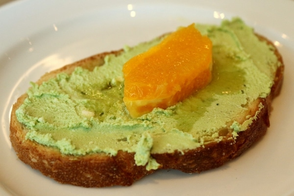 toasted bread with matcha goat cheese and an orange segment on top