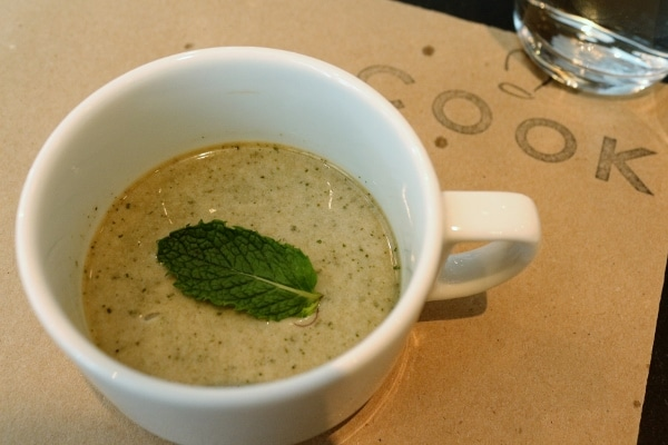 a creamy beverage in a coffee cup topped with mint