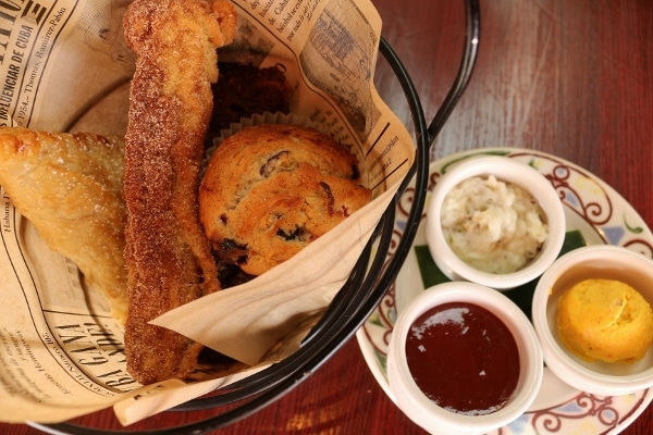 a small basket of pastries with various dipping sauces