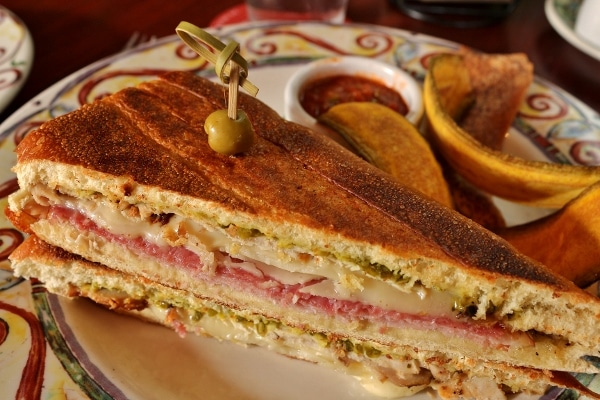 A Cuban sandwich cut in half on a plate