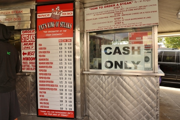 the menu and various signs outside Pat\'s King of Steaks