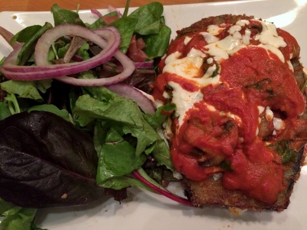 a plate of eggplant parmesan with salad on the side