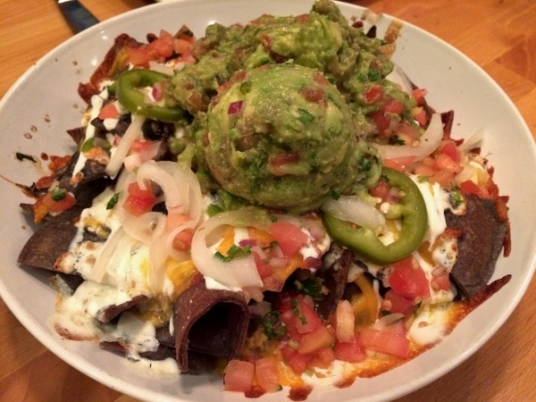 A plate of nachos topped with a large scoop of guacamole