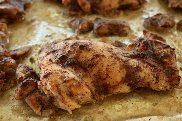 A close up of a roasted chicken thigh on a baking sheet