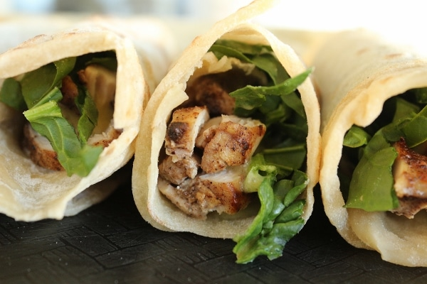 a side view of a row of chicken shawarma wraps with greens