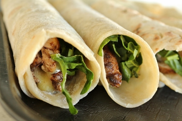 a closeup of wraps filled with chicken, greens, and sauce