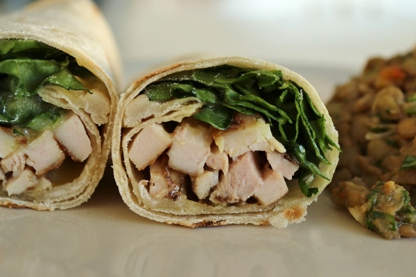 A close up of a cross-section of a wrap with chicken and greens