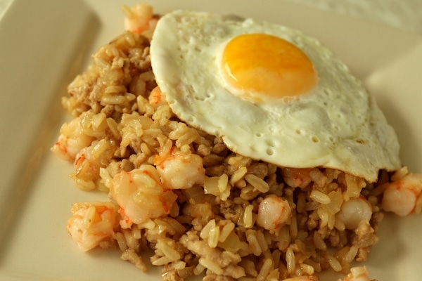 A close up of a plate of nasi goreng fried rice with shrimp and an egg