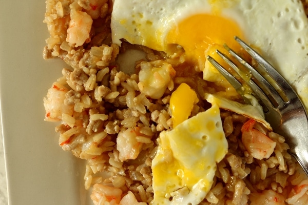 a half-eaten plate of shrimp fried rice with a fried egg on top