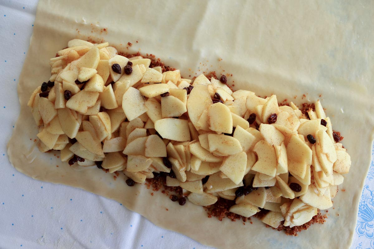 Overhead view of apple and raisin filling over stretched strudel dough.