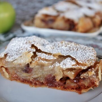 Slice of apple strudel on a plate with a platter and an apple in the background