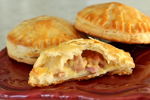 Three ham and cheese empanadas with a bite taken out of one