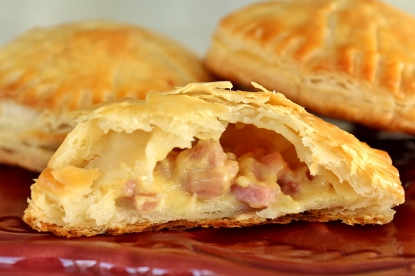 A plate of ham and cheese empanadas with the filling exposed on one of them
